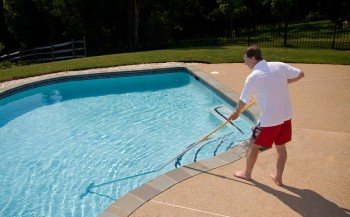 man brushing the pool