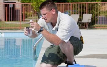 man testing swimming pool water