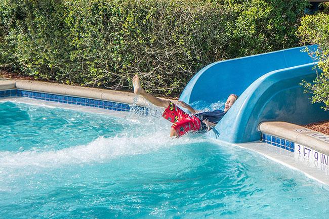 Boy enjoying the pool slide - Best Above Ground Pool Slides